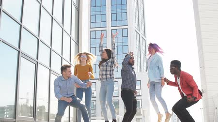 развлекательный : Group of multi ethnic young friends dressed in casual cloth having fun on lounge outdoor area on the roof of office glass building
