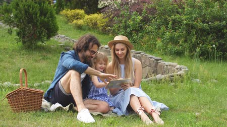 使用 : Caucasian family using digital tablet during picnic at countryside