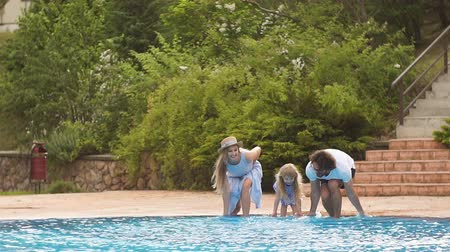two rows : Caucasian family having fun their swimming pool. Happy young family splashing water with legs or hands in swimming pool Stock Footage