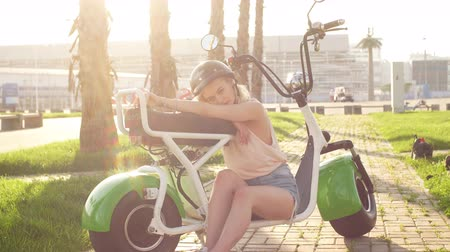rendes : Beautiful female biker of european appearance with biking helmet and glasses on head relaxing after riding on electric bike, Close-up portrait of female cyclist at summer time vacation or holiday. Stock mozgókép