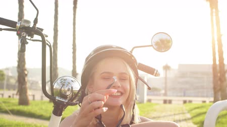 шлем : Close-up happy woman in seductive summer closing, helm, sunglasses sitting on electrocycle on stony sidewalk in urban palm parkside. Healthy lifestyle, Tourism and vacations.
