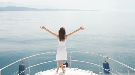 kabarık : Young woman in white dress with raised up open hands standing in the hot sun on yacht s deck over sea background with copyspace. Outdoors, lifestyle Stok Video