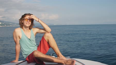 verhuizen : Caucasian man traveler floating on motorboat along sea coast with hotels and urban scape. Summer vacation at seaside. Swimming, sunbathing Wanderlust concept scene. Stockvideo