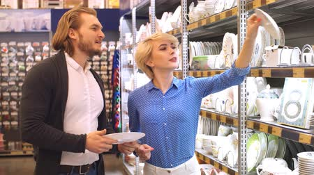giderler : Young couple shopping. Handsome young couple choosing a gift for friends birthday, deciding what dinner service to buy. Consumerism, shopping, lifestyle , fashion