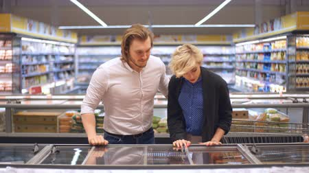 mrazák : Cute caucasian adult couple choose frozen foods from the supermarket refrigerator. Family shopping at a big trading centre in a grocery department. Dostupné videozáznamy