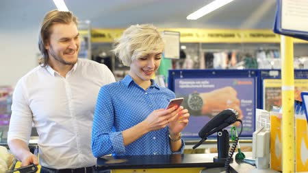 チェックアウト : Smiling young blonde lady standing in supermarket shop near cashiers desk paying with credit card, while her caucasian boyfriend watching for the purchase process.