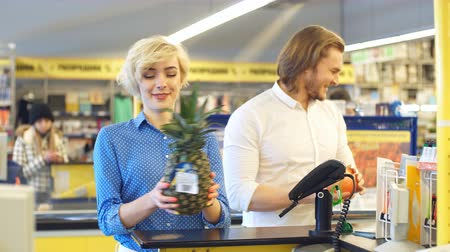 retailer : Blonde attractive woman at the supermarket checkout, she is paying using a credit card, shopping and retail concept.