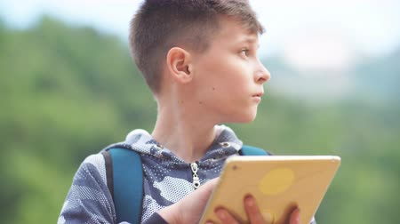 use computer : Teenager with Tablet Computer in Park. Stock Footage