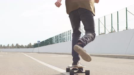 outsider : Sports Man skateboarding in Park in summer morning. man rides longboard Stock Footage