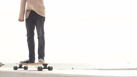 outsider : Sports Man skateboarding in Park in summer morning. man rides longboard. Slow motion
