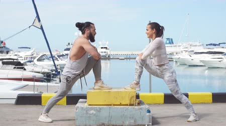 kotvící : Young fitness woman and athletic man, outdoor runners stretching legs before jogging over blue sky and ocean pier background with anchored yachts.