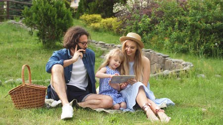 abbraccio : Caucasian family using digital tablet during picnic at countryside