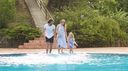 tendo : Caucasian family having fun and splashing water with legs or hands in swimming pool. trees in garden around pool