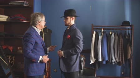 zvyk : Young, handsome and successful businessman trying on a custom made stylish suit at tailors shop. Dressmaking and Tailoring establishment concept
