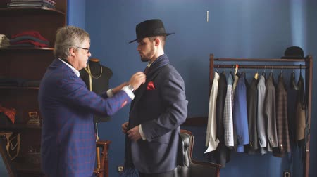 srovnávat : Young, handsome and successful businessman trying on a custom made stylish suit at tailors shop. Dressmaking and Tailoring establishment concept