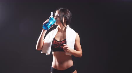 biceps : Portrait of a sports woman with towel drinking water isolated on a black background