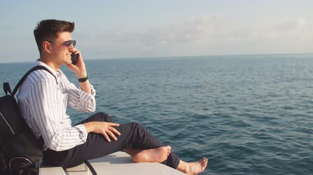 haver : Confident caucasian business man with lether backpack handling an order over the phone and with his laptop while sailing on yacht trip at sea