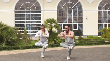 pozisyon : Professional yoga trainer and his female student conduct their outdoor training in city park area, against white building. The concept of a healthy lifestyle.