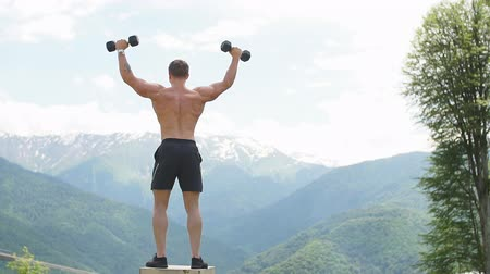 torso nudo : Strong muscular male athlete showing determination and endurance exercising muscles during body core crossfit workout in mountain landscape
