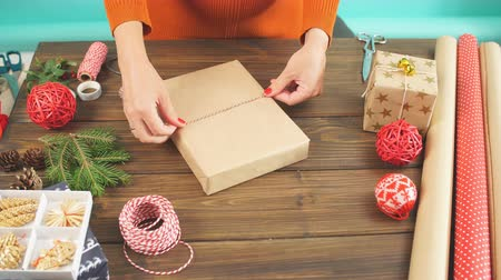 inpakpapier : Woman s hands wrapping Christmas gift on dark wooden background. Stockvideo