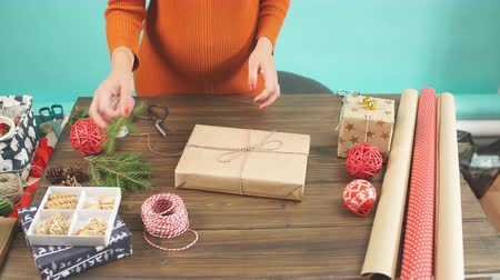 луки : Female hands decorating gift red boxes for Christmas Holiday. Hands close up. Present packaging ideas.