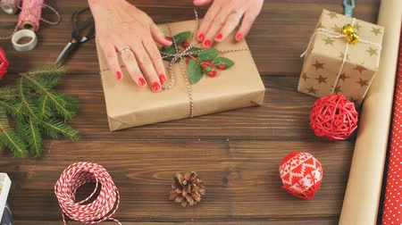 sznurek : High angle view of Christmas gift box wrapped in craft paper and tied with plain bakers twine on the dark wooden planks with decorating elements Holidays and Gifts concept. Wideo