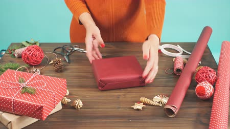 red tape : Overhead shot of female designer hands packing Christmas presents in wrapping papers on the wooden table with decorating items and Christmas baubles