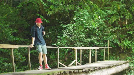 pontoon : Young caucasian Hiker in red hat and travelling clothes with backpack standing on the wooden old bridge surrounded by lush tropical forest Stock Footage