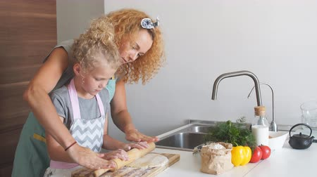 curly haired : Little Chef with the help of Mom preparing dough and ingredients of pizza, at the kitchen Stock Footage