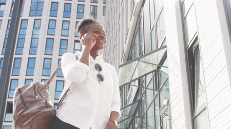 camsı : Low angle shot of african american lady, being at summer time business trip, wearing rucksack, walking along glassy business centre buildings and talking on smartphone.