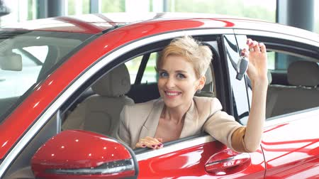 prawo jazdy : New car means new level in life. Attractive young blond woman smiling joyfully at camera and showing car key to the camera while sitting in the red shining car at auto dealership.