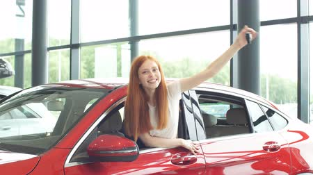 prawo jazdy : Overjoyed young red-haired driver woman screaming from joy and showing new car key while sitting in a car that she receive as gift for b-day.