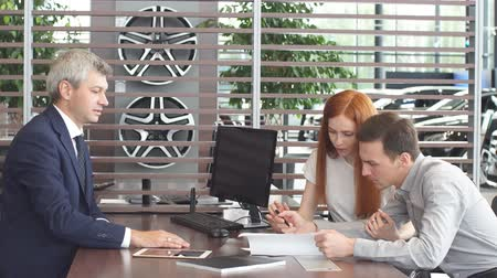 буклет : Happy positive caucasian couple signing sale contract at car dealer office, talking with sales person about vehicle insuarance