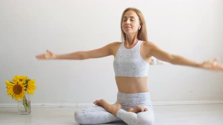 csatlakozott : Blonde european woman with tan skin listens relaxing music in wireless earphones, sitting with joined hands in namaste gesture, smiling and closing eyes, meditating in white studio Stock mozgókép