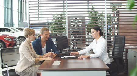 буклет : Agreement or contract concept. Confident young female sales manager offering car purchase contract to young couple at car dealership office. Стоковые видеозаписи