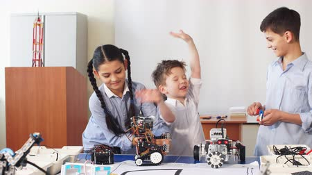 helpful : Group of happy kids of different age choose parts of robotic electric toys for building robots at robotics school lesson. Stock Footage