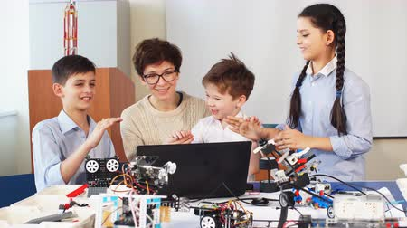 bütünleşme : education, science, technology, children and people concept , Pleasant young engineer mother showing her children using laptop how to construct and programme plain robot kits Stok Video