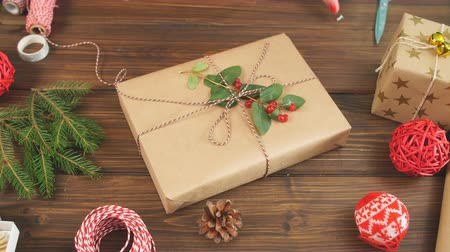 sicim : Christmas presents wrapped in eco paper with homemade decoration on wooden background with decor elements and units Stok Video