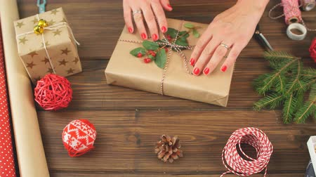 caja roja : Woman s hands wrapping Christmas gift on dark wooden background. Archivo de Video