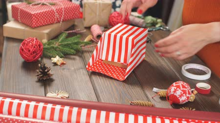 inpakpapier : Overhead shot of female designer hands packing Christmas presents in wrapping papers on the wooden table with decorating items and Christmas baubles