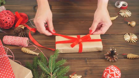 unready : Christmas flat lay of unready hand crafted gift box on rustic wooden table with rolls of craft and colour wrapping paper, pine cones, fir branches and decor elements.