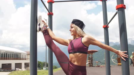 quads : Active blonde female in sports clothes, demonstrates her flexibility and does vertical splits, stretches legs near high horizontal bar . People, sport training concept
