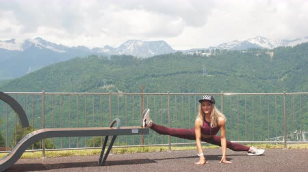 quads : Active blonde female in sports clothes, demonstrates her flexibility and does splits, stretches legs against against green mountains with trees background.