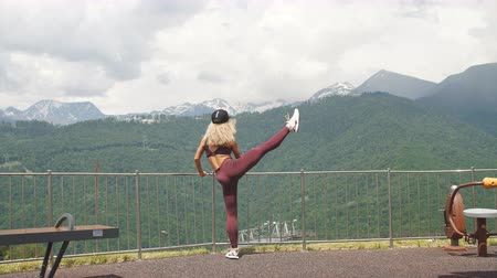 quads : Athletic woman with long blonde hair doing vertical single leg split exercise outdoors enjoying gorgeous mountain landscape background. Stock Footage