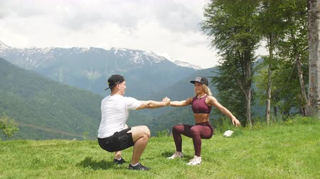 squat : Athletic woman doing exercise with her male partner outdoors over high mountains in background. Stock Footage