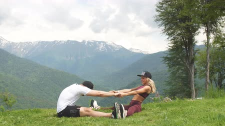 zadek : Athletic woman doing exercise with her male partner outdoors over high mountains in background