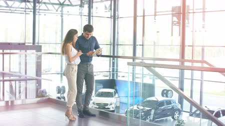 буклет : Young handsome caucasian businessman reading an advertising booklet at the car dealership while his beautiful wife embracing him, standing nearby. Стоковые видеозаписи