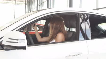prawo jazdy : Happy caucasian young female driver sitting in white car shows car keys at auto showroom