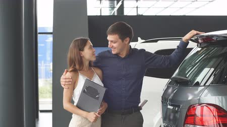 ırklararası : Making a decision. Beautiful young couple choosing a new car at the car dealership, sitting at the car trank and study car features.