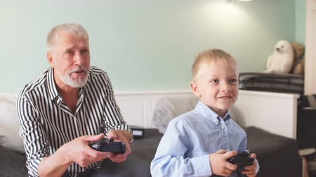 ped : Cute little boy with grandfather sitting on sofa and playing video game with game pad